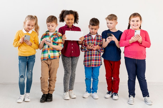 Young childrens with different devices Free Photo