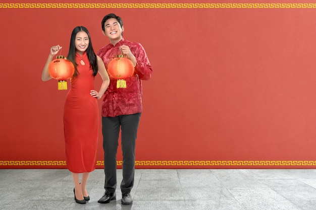 Young chinese couple with traditional dress holding red lanterns Premium Photo