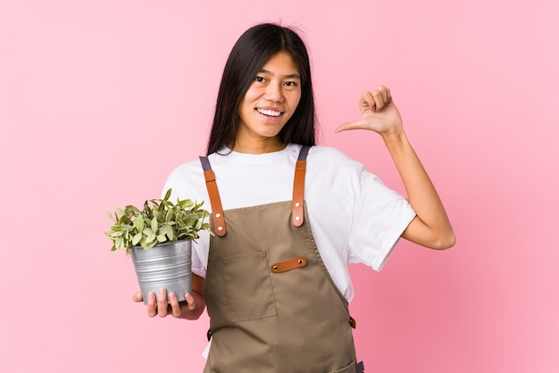 Young chinese gardener woman holding a plant isolated feels proud and self confident, example to follow. Premium Photo