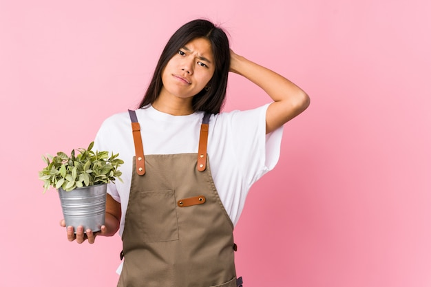Young chinese gardener woman holding a plant isolated touching back of head, thinking and making a choice. Premium Photo