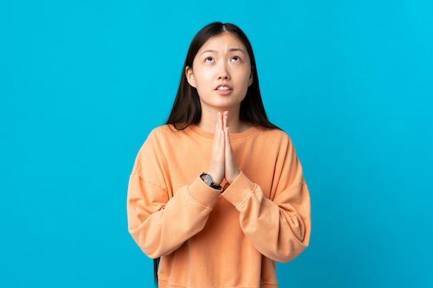 孤立した青い壁の上の若い中国人の女の子が一緒に手のひらを保つ Premium写真