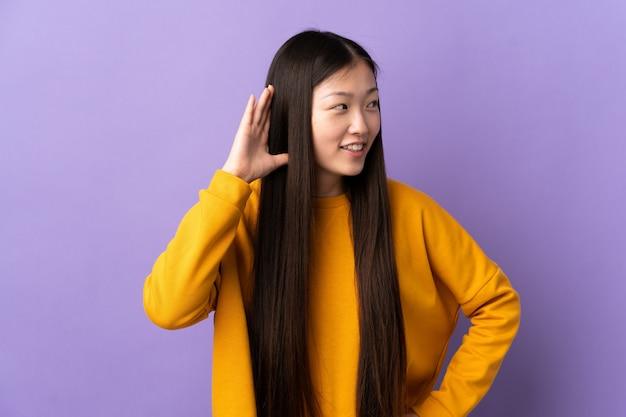 Молодая китайская девушка над изолированной фиолетовой стеной слушая что-то кладя руку на ухо Premium Фотографии