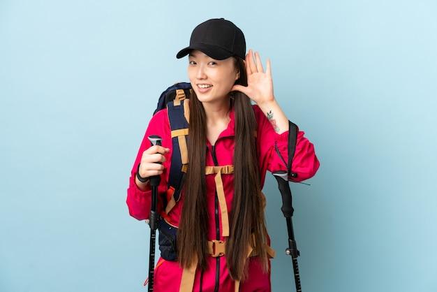 Молодая китайская девушка с рюкзаком и треккинг поляков над синей стеной, слушая что-то, положив руку на ухо Premium Фотографии