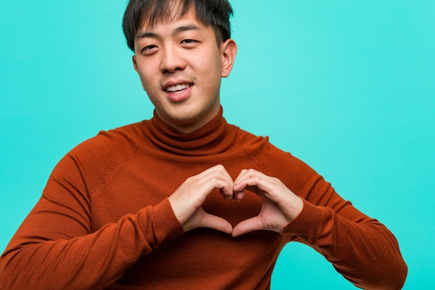 Young chinese man doing a heart shape with hands Premium Photo