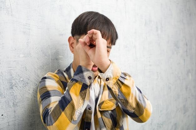 Молодой китаец лицо крупным планом, делая жест подзорной трубы Premium Фотографии