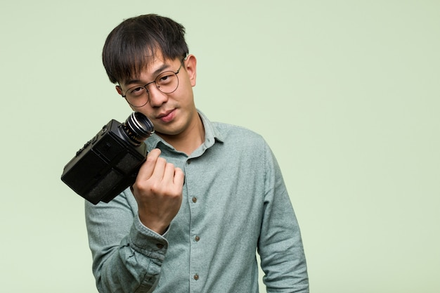 Young chinese man holding a vintage camera inviting to come Premium Photo