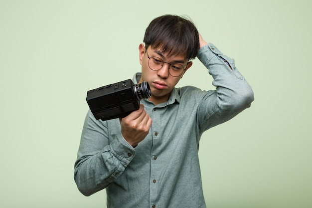 Young chinese man holding a vintage camera worried and overwhelmed Premium Photo