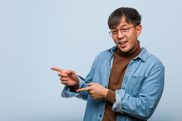 Young chinese man pointing to the side with finger Premium Photo