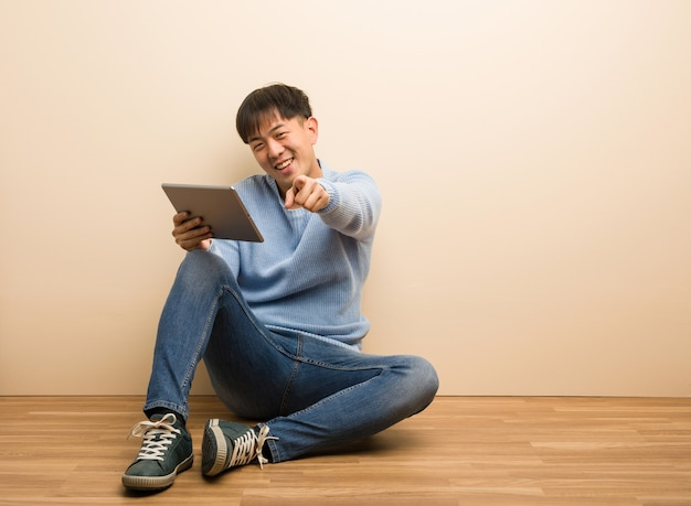 Young chinese man sitting using his tablet cheerful and smiling pointing to front Premium Photo