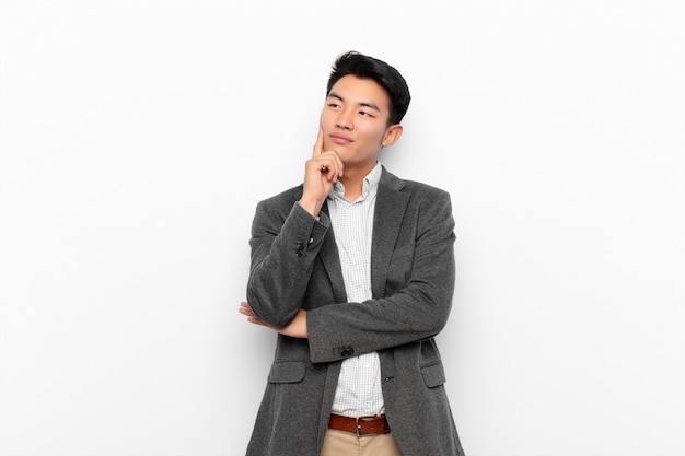 Young chinese man smiling happily and daydreaming or doubting, looking to the side on flat color wall Premium Photo