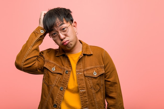 Young chinese man wearing a jacket worried and overwhelmed Premium Photo