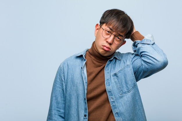 Young chinese man worried and overwhelmed Premium Photo