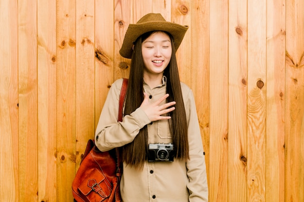 Young chinese traveler woman laughs out loudly keeping hand on chest. Premium Photo