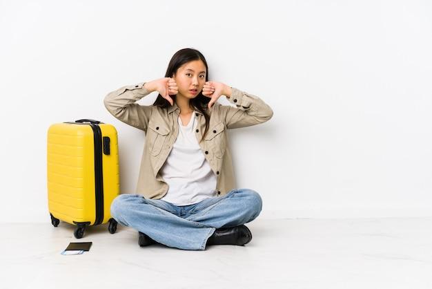 搭乗券を持って座っている若い中国人旅行者の女性が親指を示し、嫌悪感を表現します。 Premium写真
