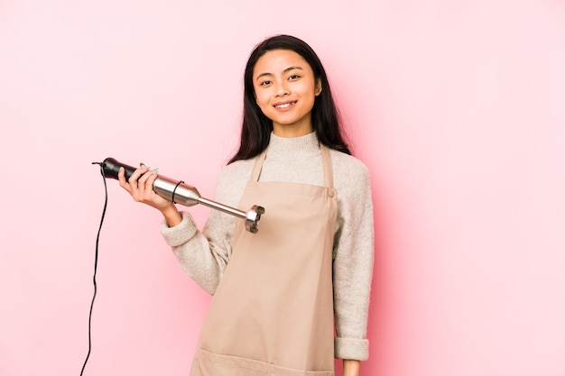 シャツのコピースペースを手で指しているミキサー孤立した人を保持している若い中国人女性、誇りと自信を持って Premium写真