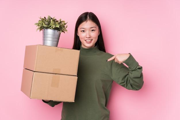 自信を持って自信を持ってシャツのコピースペースを手で指している孤立したボックスを保持している若い中国人女性 Premium写真