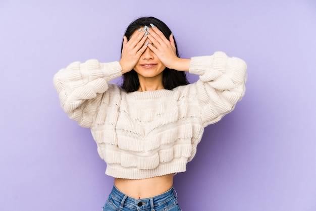 Young chinese  woman isolated on a purple background covers eyes with hands, smiles broadly waiting for a surprise. Premium Photo