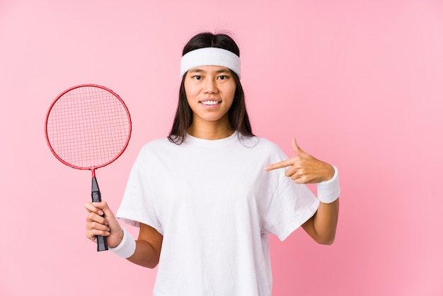 Young chinese woman playing badminton in a pink wall person pointing by hand to a shirt copy space, proud and confident Premium Photo