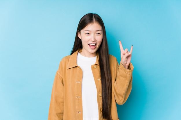 Молодая китайская женщина представляя в голубой стене изолировала показывать жест рожков как концепция революции. Premium Фотографии