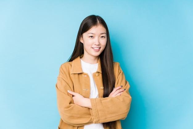 自信を持って、決意を持って腕を組んでいる孤立した青い壁でポーズをとる若い中国人女性。 Premium写真