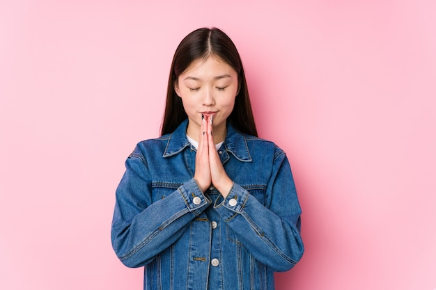 Young chinese woman posing in a pink wall isolated holding hands in pray near mouth, feels confident. Premium Photo