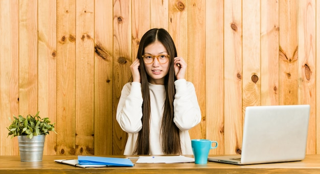 Young chinese woman studying on her desk covering ears with hands. Premium Photo