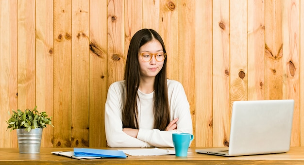 Young chinese woman studying on her desk frowning face in displeasure, keeps arms folded. Premium Photo