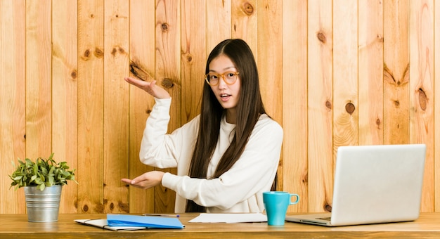 Young chinese woman studying on her desk shocked and amazed holding a  between hands. Premium Photo