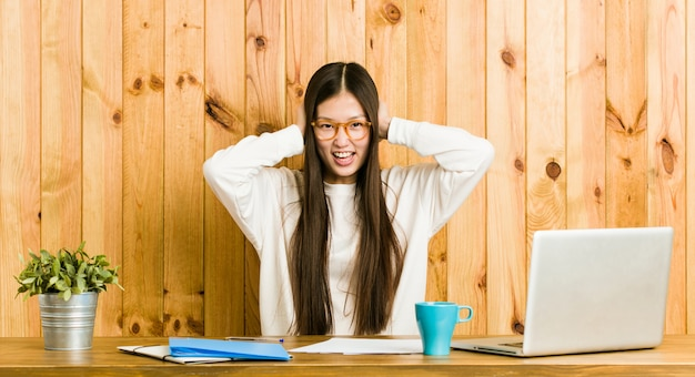 Молодая китайская женщина изучая на ее ушах заволакивания стола с руками пробуя не услышать слишком громкий звук. Premium Фотографии