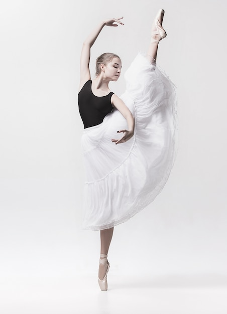 Young classical dancer dancing on white. ballerina project. Free Photo