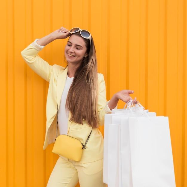 노란색 옷을 입고 선글라스를 들고 젊은 클라이언트 무료 사진