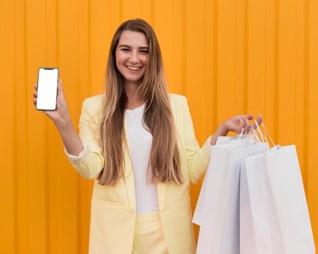 Giovane cliente che indossa vestiti gialli e che tiene un telefono Foto Gratuite