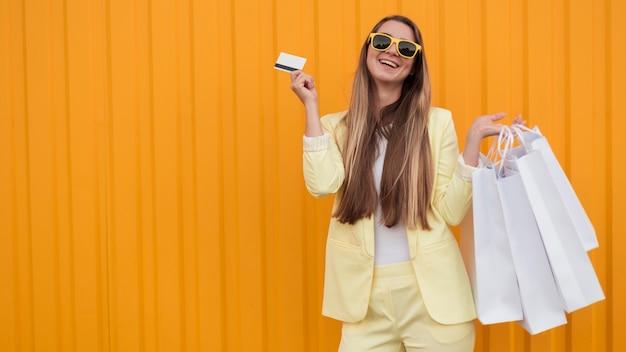 쇼핑 카드를 들고 노란색 옷을 입고 젊은 클라이언트 프리미엄 사진