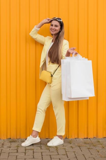 노란색 옷을 입고 젊은 클라이언트 롱 샷 무료 사진