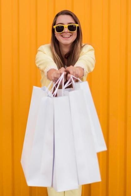 彼女の買い物袋を示す黄色の服を着ている若いクライアント 無料写真