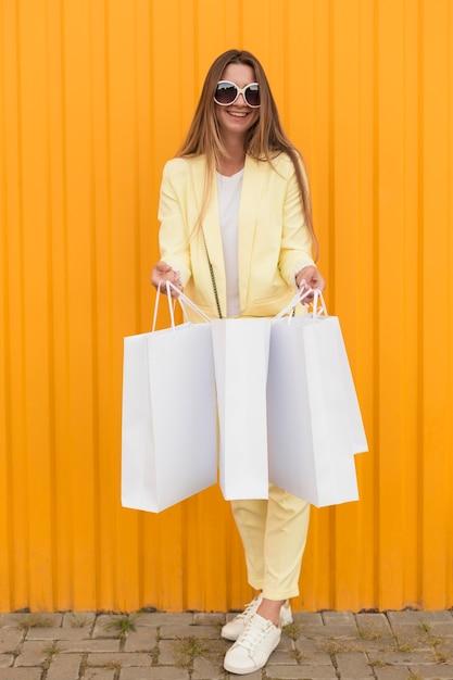 白い袋と黄色の服を着ている若いクライアント 無料写真