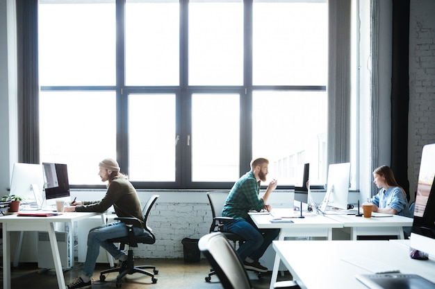젊은 동료 컴퓨터를 사용하여 사무실에서 일 무료 사진