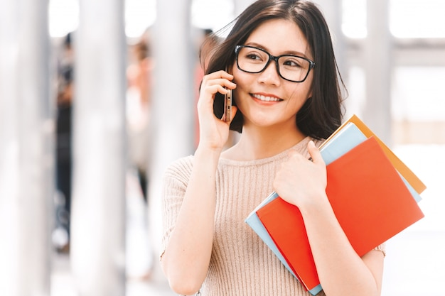 Young college woman holding book walking and using a smartphone in campus Premium Photo