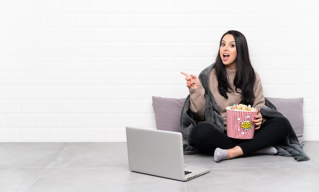 Young colombian girl holding a bowl of popcorns and showing a film in a laptop surprised and pointing finger to the side Premium Photo