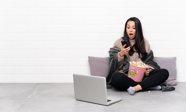 Young colombian girl holding a bowl of popcorns and showing a film in a laptop surprised and sending a message Premium Photo