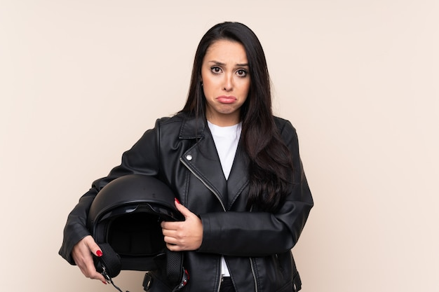 Young colombian girl holding a motorcycle helmet over wall sad Premium Photo