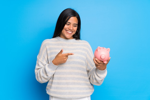 Young colombian girl with sweater holding a piggybank Premium Photo