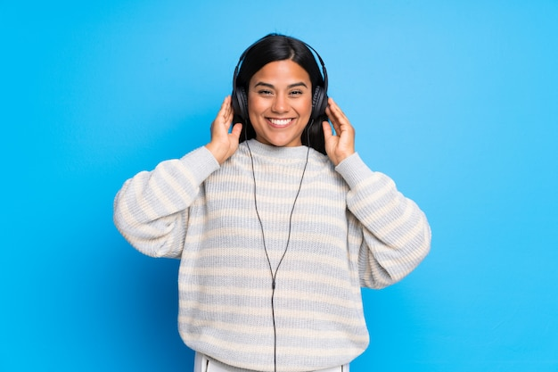 Young colombian girl with sweater listening to music with headphones Premium Photo