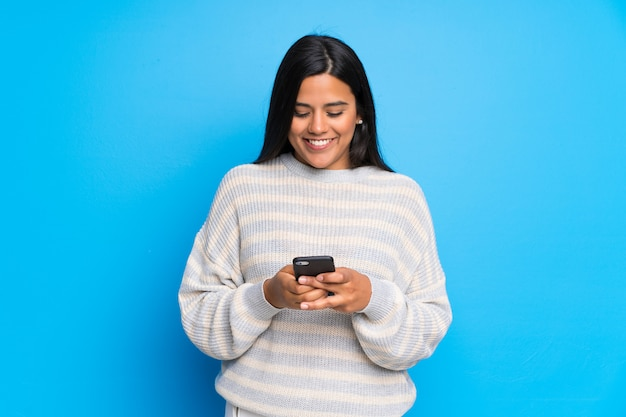 Young colombian girl with sweater sending a message with the mobile Premium Photo