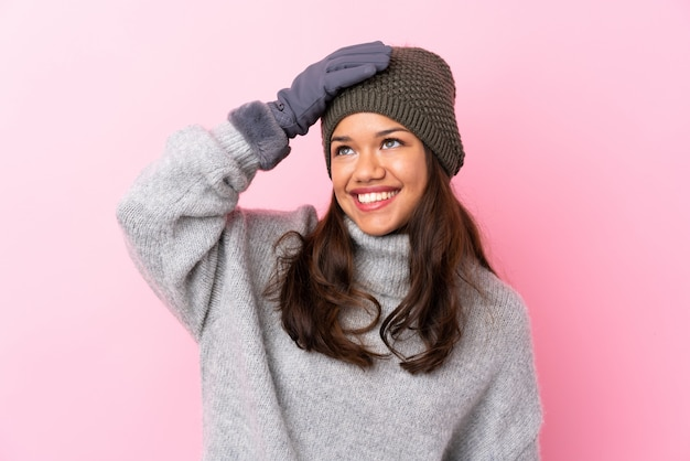 Young colombian woman with winter hat over isolated pink wall laughing Premium Photo