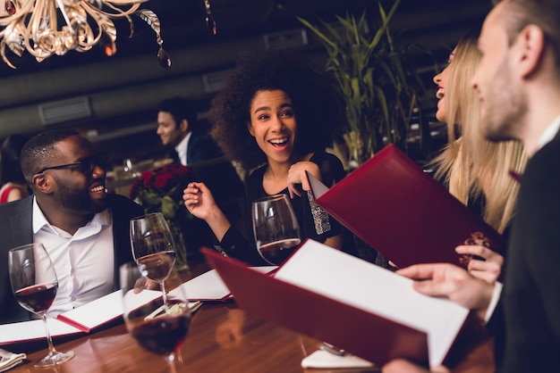 A young company is sitting together in a restaurant. Premium Photo