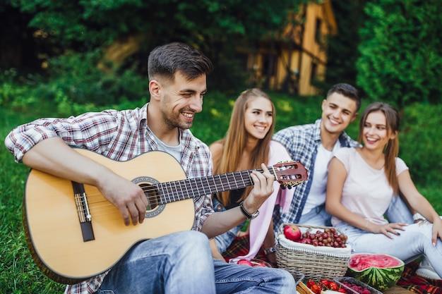 Молодая компания студентов проводит выходные в парке, а один брюнет играет на гитаре. Premium Фотографии