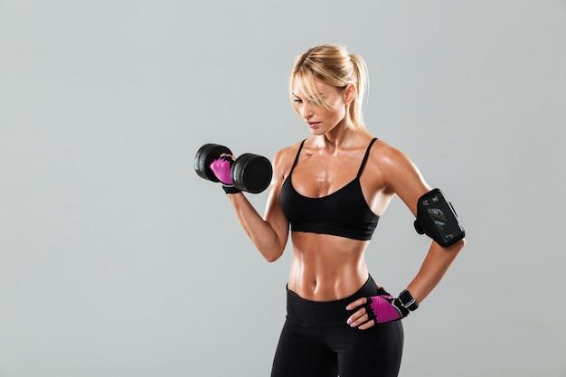 Молодая сконцентрированная женщина спортсмена делая тренировки с гантелью Бесплатные Фотографии