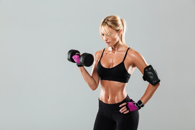 Young concentrated athlete woman doing exercises with a dumbbell Free Photo