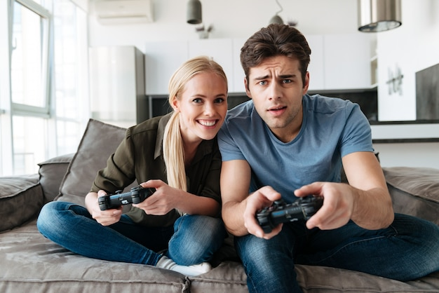 Young concentrated man and woman playing video games in living room Free Photo